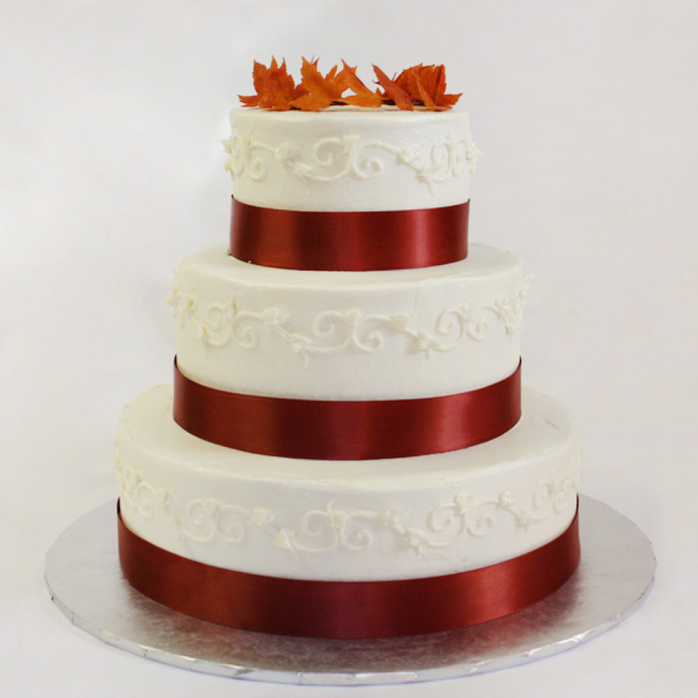Свадебный торт с красной лентой и осенней листвой