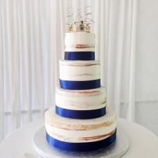 Свадебный торт с синей лентой и фигурками молодоженов